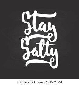 Hand drawn typography lettering phrase Stay Salty isolated on the black chalkboard background. Fun calligraphy for typography greeting and invitation card or t-shirt print design.