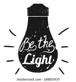Hand drawn typography poster. Motivation quote Be the light  isolated on light bulb background. Calligraphy lettering vector illustration for home decoration.