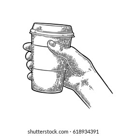 Hand holding a disposable cup of coffee with cardboard holder and cap. Vintage black vector engraving illustration for label, web, flayer. Isolated on white background