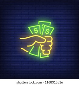 Hand holding dollar bills neon sign. Money, finance and banking concept. Advertisement design. Night bright neon sign, colorful billboard, light banner. Vector illustration in neon style.