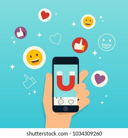 Hand holding mobile smart phone with magnet attracting hearts and reaction smileys. Social media marketing concept.
