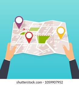 Hand holding a paper map. Tourist look at map of the city. Vector Illustration in flat design. Travel concept.