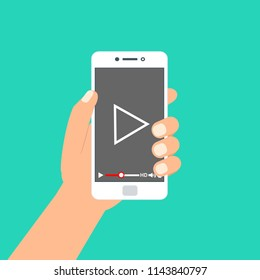 """Hand holding phone icon. Vector illustration. There is a """"play"""" button on the display of the smartphone in the picture"""