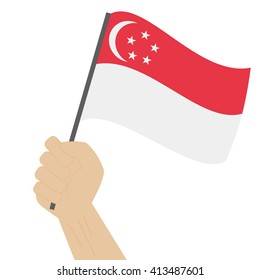 Hand holding and raising the national flag of Singapore