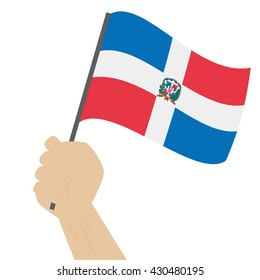 Hand holding and raising the national flag of Dominican Republic