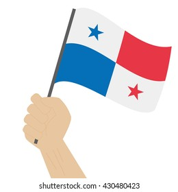 Hand holding and raising the national flag of Panama