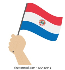 Hand holding and raising the national flag of Paraguay