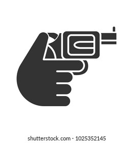Hand holding revolver glyph icon. Silhouette symbol. Shooting. Russian roulette. Pistol, gun. Negative space. Vector isolated illustration