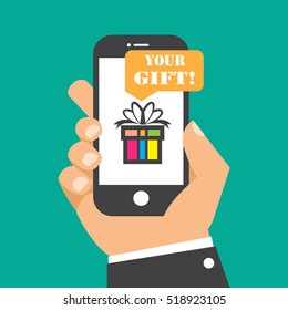 Hand holding smartphone with gift box on the screen.