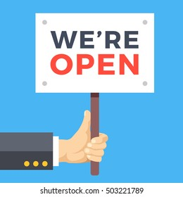 Hand holding we are open banner. Wooden sign, paper placard with title. Store opening, business hours concepts. Modern vector illustration