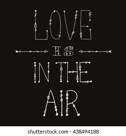 hand lettering - love is on the air - on the dark grey background with hand drawing arrows