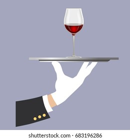 Hand of the waiter in a white glove with a glass of wine on a tray
