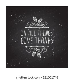 Handdrawn thanksgiving label with acorns and text on chalkboard background. In all things give thanks.