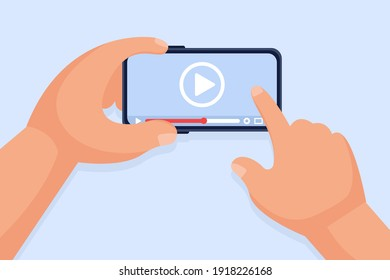Hands hold a smartphone and touch the screen. Video player on the screen. Video content marketing concept. Online training, video conferencing and webinars, publishing information in video.