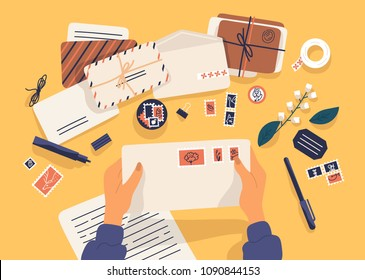 Hands holding envelope with stamps surrounded by papers, postcards, pen on yellow background. Top view. Postcrossing, sending letters through postal service. Flat cartoon vector illustration