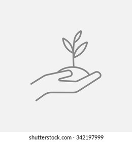 Hands holding seedling in soil line icon for web, mobile and infographics. Vector dark grey icon isolated on light grey background.