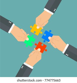 Hands putting puzzle pieces together. Teamwork concept