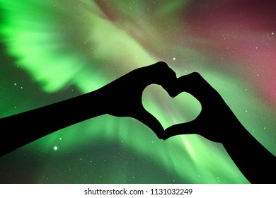 Hands in shape of heart at night. Vector illustration with silhouette of hands, showing shape of heart. Northern lights in starry sky