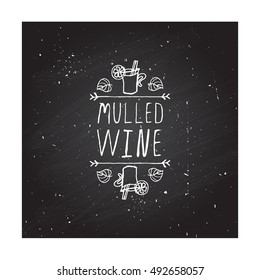 Hand-sketched typographic element with mulled wine, leaves and text on blackboard background. Mulled wine