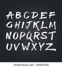 Handwritten calligraphic white alphabet written with brush pen on black chalkboard background. Handmade abc font typography