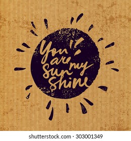 Handwritten inspirational quote 'You are my sunshine'. Expressive brush lettering and sun drawing on vintage grunge background.  Vector illustration.