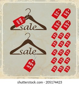 """Hangers with tags and word """"sale"""" on grunge background"""