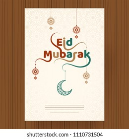 Hanging crescent moon and floral elements decorated stylish text Eid Mubarak. Greeting card design on wooden background.