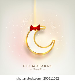 Hanging golden moon with red ribbon on beige background for muslim community festival Eid Mubarak.