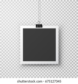Hanging photo frame with paper clip. Black square snapshot and metal blinder isolated on transparent background. Vector picture hang on paperclip for your design.