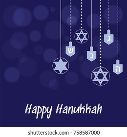Hanukkah blue background with hanging star of David and dreidel and the blurred spots of light.