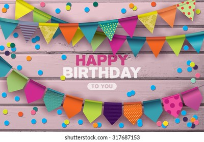 Happy Birthday card with colorful paper garlands and confetti on pink wooden background.