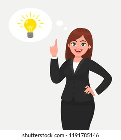 Happy business woman pointing hand up and bright light bulb appearing in the thought bubble. Idea and innovation concept illustration in cartoon vector style.