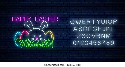 Happy easter glowing signboard with bunny and colored eggs on grass with alphabet in neon style on dark brick wall background. Easter funny greeting banner. Vector illustration.