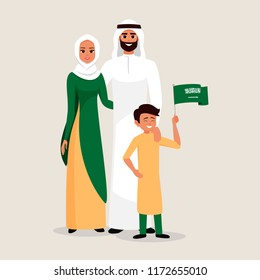 Happy family celebrating the Independence Day of Saudi Arabia. Smiling Father, mother and son holding the flag of Saudi Arabia.
