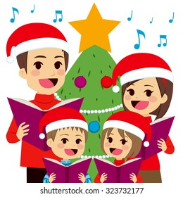 Happy family singing carols in front of Christmas tree at home