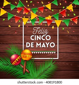 Happy Fifth May Mexican greeting card or poster with Mexican text in a frame over a wood background decorated with flag bunting and musical rattles