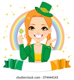 Happy girl dressed as leprechaun celebrating Saint Patrick day holding luck green clover shamrock