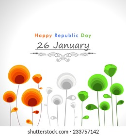 Happy Indian Republic Day celebration concept with beautiful text and flowers in national flag colors on shiny grey background.