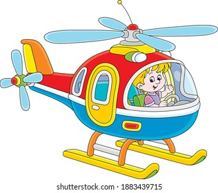 Happy little boy playing and piloting a big and colorful toy helicopter on a playground, vector cartoon illustration on a white background