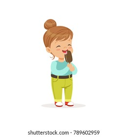 Happy little girl eating delicious chocolate ice-cream on stick. Cartoon child character with brown hair in blue blouse and green pants with belt. Flat vector design