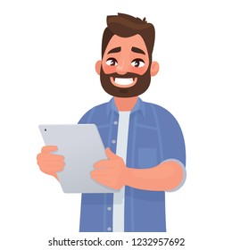 Happy man holding tablet computer in his hands. Vector illustration in cartoon style.