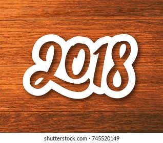 Happy New Year 2018 paper label with calligraphic number on wood background. Vector greeting card design template for winter holidays