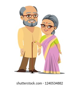 A happy old Indian couple is standing together. The man is tall and bald and the woman is short and plump and is holding a walking stick. They are both wearing eye glasses.