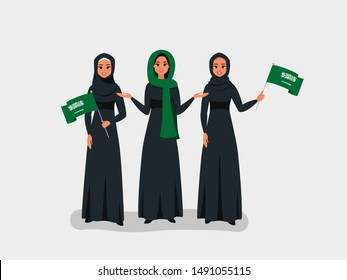 Happy Saudi women celebrate the Independence Day of the Kingdom of Saudi Arabia. Muslim girls dressed in black Abaya hold the KSA flags on the national day-September 23.