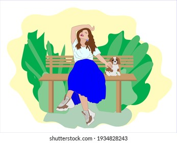 Happy smiling woman sits on a Park bench with her dog and caressing it.