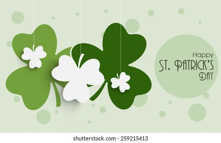 Happy St. Patrick's Day celebration with hanging shamrock leaves on green background.