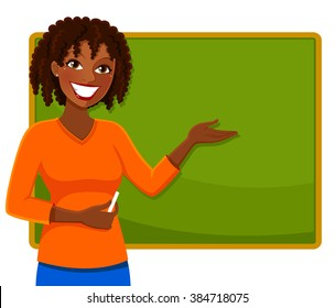 happy teacher of African ethnicity standing next to a blackboard