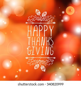 Happy Thanksgiving. Hand sketched graphic vector element with acorns and text on blurred background.
