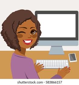 Happy young African American woman using desktop computer