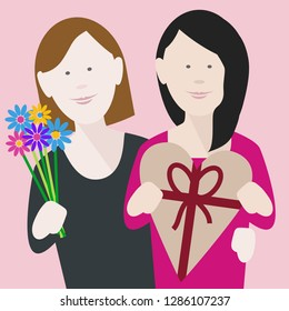 happy young lesbian couple in love exchanging gifts on saint valentine's day